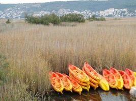 gelbe und orangefarbene Kyaks in der Nähe eines Restaurants, Kroatien