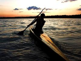 Kajakfahrer im Wasser gegen den Sonnenuntergang foto