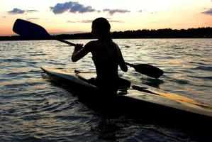 Silhouette der Kajakfahrerin in der Mitte eines Sees foto