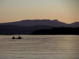 Kajakfahrer bei Sonnenuntergang mit lila Himmel. foto