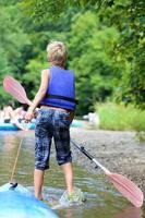 aktiver Junge, der Kajakfahren auf dem Fluss während des Sommerlagers genießt