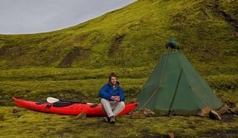 Mann sitzt auf Kajak auf dem Campingplatz foto