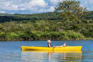 ruhiger Fluss und Frau, die in einem Kajak entspannt foto