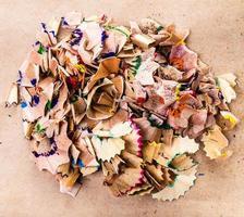 Haufen Farbstiftrasuren isoliert auf braunem Recyclingpapier foto