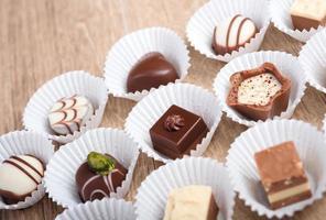 hölzerner Hintergrund mit einer Reihe von Schokoladenpralinen foto