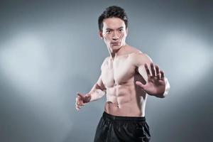 muskulöser asiatischer Kung-Fu-Mann in Aktionspose. foto