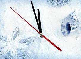 uhr mit tannenzweigen und weihnachtsschmuck unter schnee clo foto