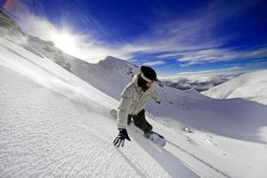 Action-Aufnahme von Snowboarder, der den Berg hinunter rast foto
