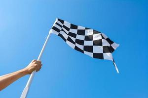 Hand, die Zielflagge auf blauem Himmelhintergrund hält foto