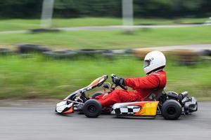 Schwenkaufnahme des Go-Kart-Rennfahrers foto
