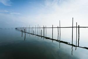 Die Brücke befindet sich in einer ruhigen Seeoberfläche foto