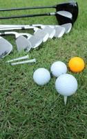 Golfball und Golfschläger in Tasche auf grünem Gras foto