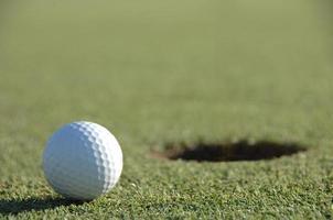 Golfball auf dem Grün in der Nähe des Lochs