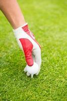 Golfer platziert Golfball auf Tee foto