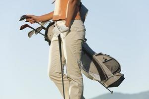 Italien, Kastelruth, Frau auf Golfplatz mit Golftasche foto