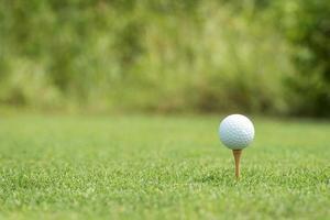 Golfball auf einem weißen Tee foto
