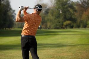 junger Mann schwingenden Golfschläger, Rückansicht foto