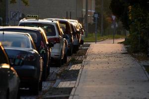 Parken von Autos mit einem Taxi auf dem Bürgersteig foto