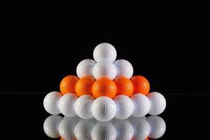Pyramide von Golfbällen auf einem schwarzen Hintergrund foto