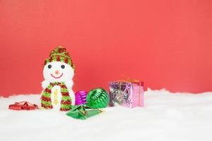 Schneemann und weiße Weihnachtskugeln mit Geschenk foto