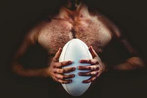hemdloser Rugbyspieler, der Ball hält foto