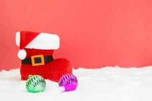 Santa Stiefel und weiße Weihnachtskugeln auf rotem Hintergrund, Konzept foto