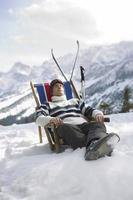 Mann, der auf Liegestuhl in den schneebedeckten Bergen ruht foto