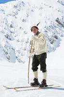 junger Vintage-Skifahrer, der in den Bergen aufwirft