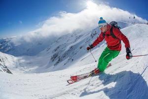Skifahrer Skifahren bergab im Hochgebirge gegen Sonnenuntergang