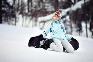junge weibliche Snowboarderin sitzt