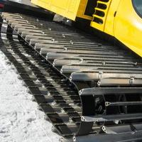 gelbes Kettenfahrzeug auf Schnee, Putzmaschine