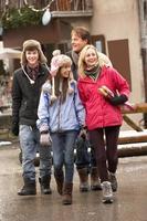 Teenager-Familie, die entlang der verschneiten Stadtstraße im Skigebiet geht