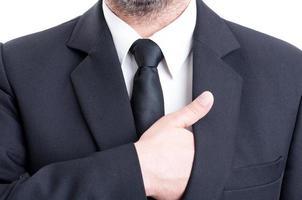 Geschäftsmann, der Hand in Anzugjacke einführt