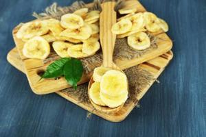 frische und getrocknete Bananenscheiben auf hölzernem Hintergrund foto