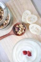 Müsli auf Löffel mit Joghurtschale foto