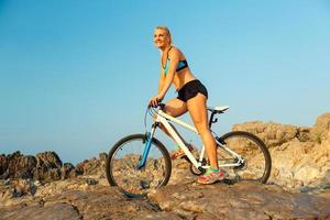 glückliche athletische Frau, die auf den Felsen mit einem Fahrrad steht