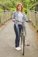 hübsche Rothaarige mit ihrem Fahrrad, das in die Kamera lächelt