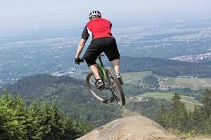 Mountainbike-Fahrer springt Abgrund foto