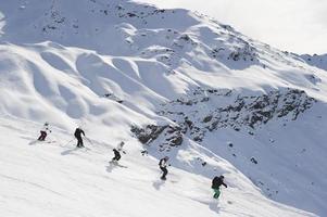 Skifahrer, die zusammen auf der Piste Ski fahren foto