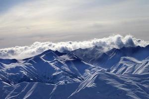 schneebedeckte Berge im Nebel am Winterabend