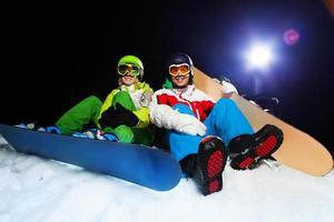 zwei lächelnde Snowboarder, die nachts sitzen