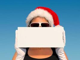 attraktive Frau mit Weihnachtsmütze, die ein Zeichen hält