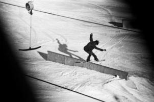 Pro Snowboarder rutscht auf der Schiene foto