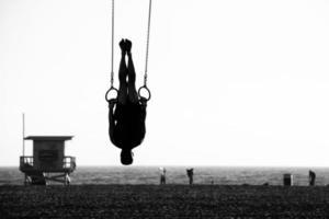 Silhouette einer Person, die auf Ringen schwingt foto