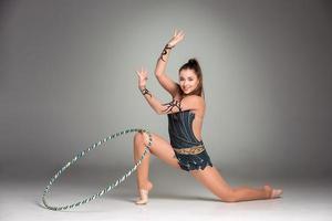 Teenager, der Gymnastikübungen mit buntem Reifen macht foto