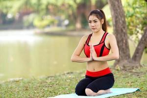 junge hübsche Frau, die Yogaübungen im Park macht foto