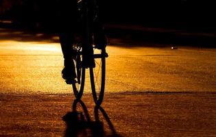 Silhouette der Radfahrer, die Fahrrad auf Straße fahren foto