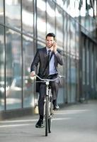 Geschäftsmann, der mit Handy spricht und Fahrrad fährt foto
