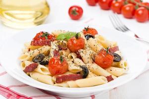 Nudeln mit Wurst, Kirschtomaten und Oliven auf dem Teller foto