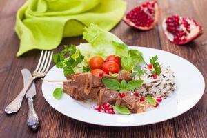 Kebab und Wildreis mit frischem Gemüse und Granatapfelkernen